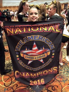 Ashley holds the most recent national championship banner she won in Buffalo, NY.